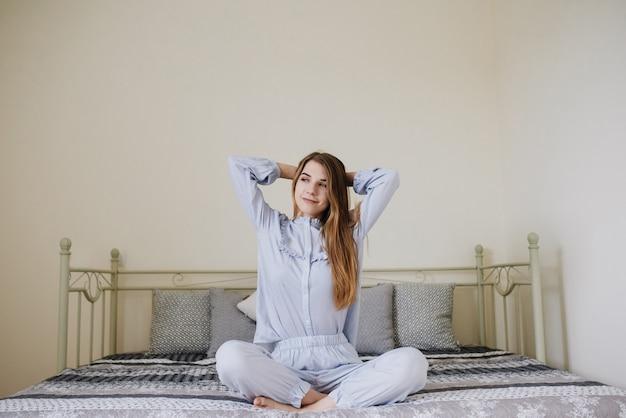 Het meisje werd wakker en ging in haar pyjama zitten op het bed in haar kamer. stijlvol grijs-wit interieur. het meisje rekt zich uit. Premium Foto