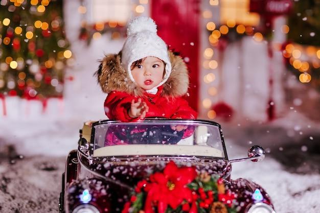 Het meisje zit in een rode kinderen converteerbaar Premium Foto