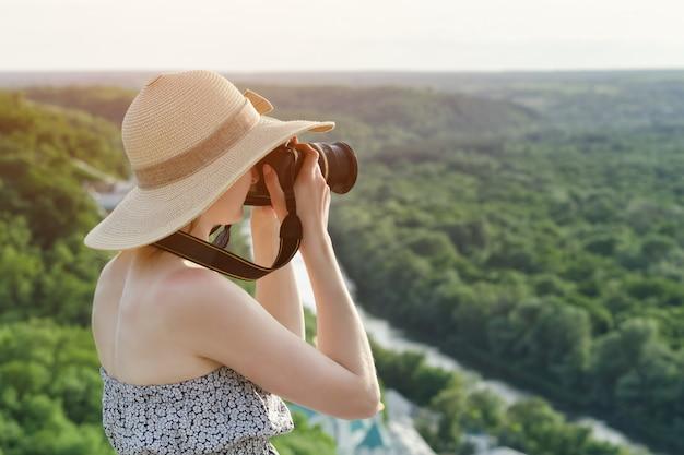 Het meisje zit op een heuvel en maakt foto's tegen het bos en de rivier Premium Foto
