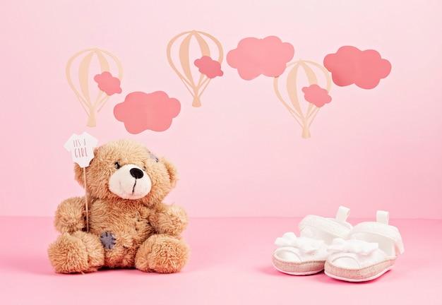 Het meisjes leuke roze schoenen van de baby over de roze pastelkleurachtergrond met wolken en impulsen Premium Foto