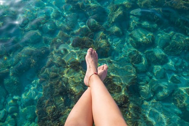 Het meisjesbenen van ibiza bij het duidelijke water van het strand portinatx Premium Foto
