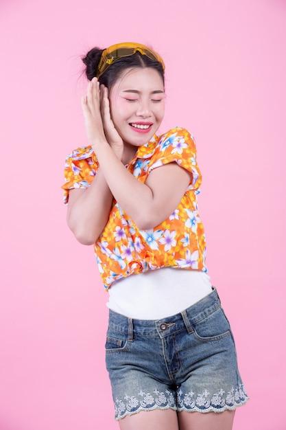 Het meisjeskleding van de manier omhoog met handgebaren op een roze achtergrond. Gratis Foto