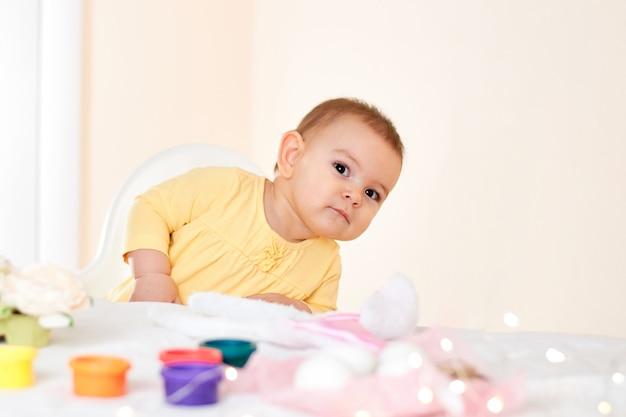 Het meisjeszitting van de baby bij de lijst en het schilderen vakantiepaaseieren die gelukkige kinderjaren glimlachen Premium Foto