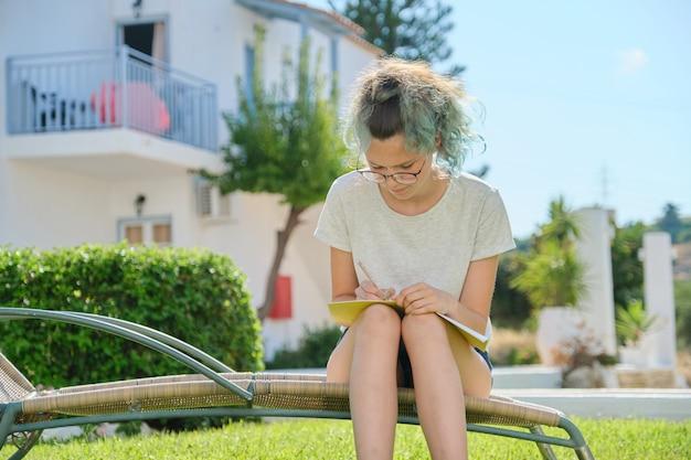 Het meisjeszitting van de student openlucht, schrijvend in schoolnotitieboekje Premium Foto