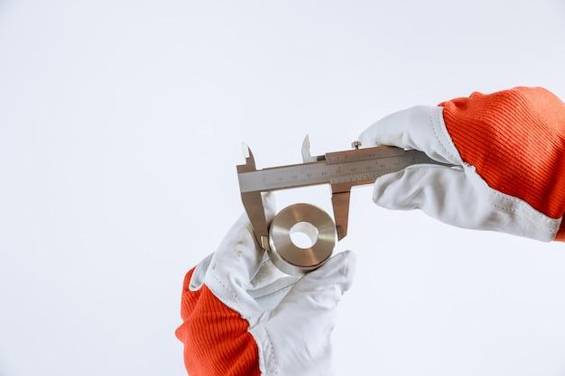 Het meten van binnendiameter, buitendiameter, lengte met een schuifmaat op een witte achtergrond. meetnauwkeurigheid. Premium Foto