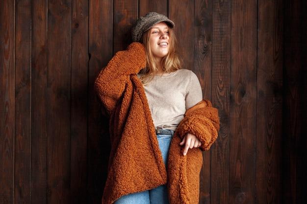 Het middelgrote geschotene smileyvrouw stellen met houten achtergrond Gratis Foto