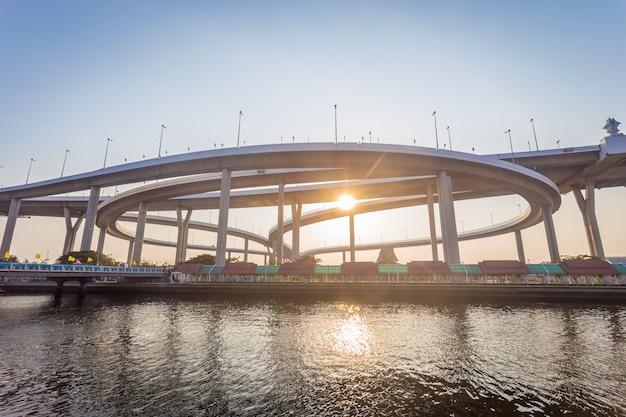 Het moderne beton overbrugt de manieren over grote rivier in zonsondergangtijd met zonlicht. Premium Foto