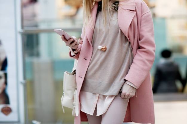 Het modieuze jonge meisje die zich in een roze laag in een winkel bevinden en onderzoekt de telefoon Premium Foto
