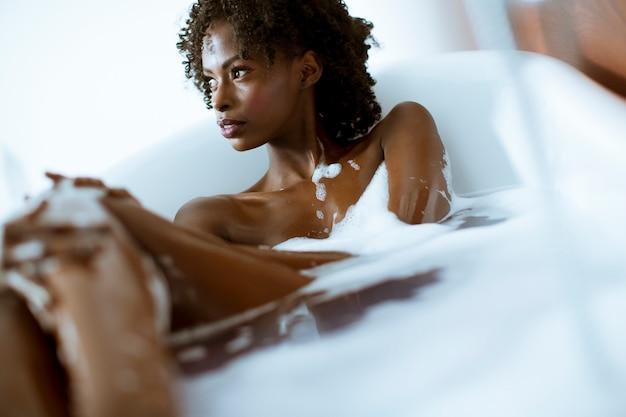 Het mooie afrikaanse amerikaanse vrouw baden in een tonhoogtepunt van schuim Premium Foto