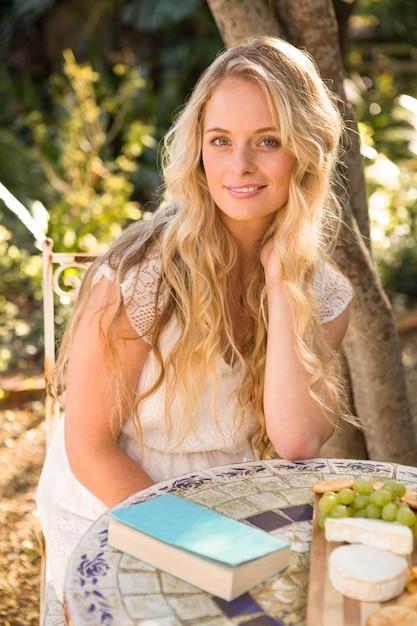 Het mooie blonde ontspannen met een boek en voedsel in de tuin Premium Foto