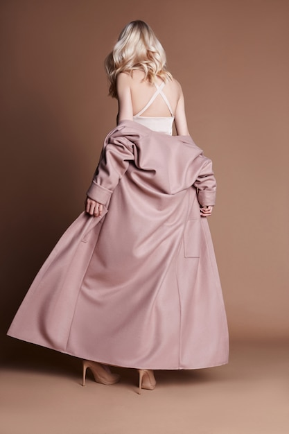 Het mooie blondevrouw stellen in een roze laag op een beige Premium Foto