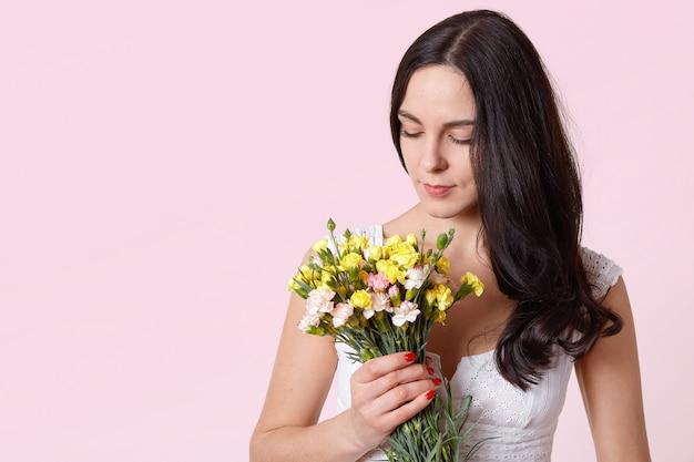 Het mooie boeket van de meisjesholding van bloemen dat op roze, donkerbruin wijfje wordt geïsoleerd dat neer op haar huidig kijkt Gratis Foto
