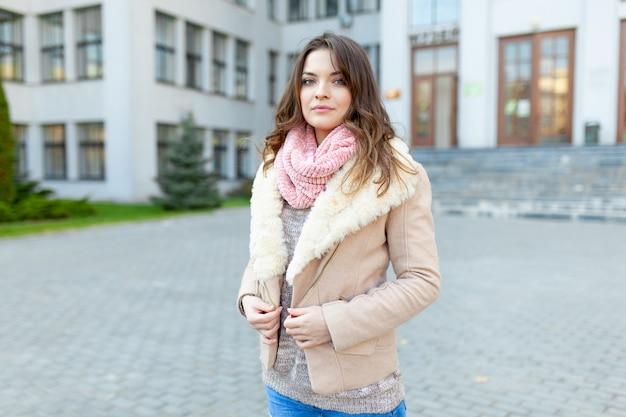 Het mooie europese meisje kleedde warme de herfstkleren loopt straten met bureaugebouwen Premium Foto