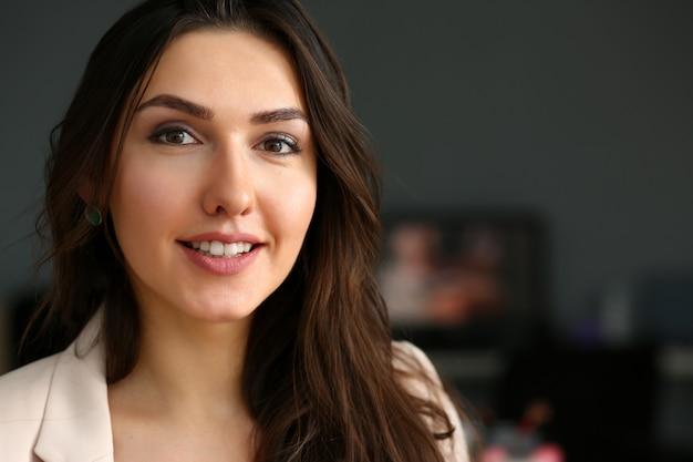 Het mooie glimlachende meisje op werkplaats kijkt in camera Premium Foto