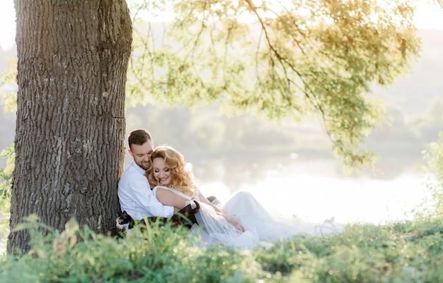 Het mooie glimlachende paar zit in openlucht op het groene gras dichtbij boom, romantische picknick, gelukkige familie op de zonnige dag Gratis Foto
