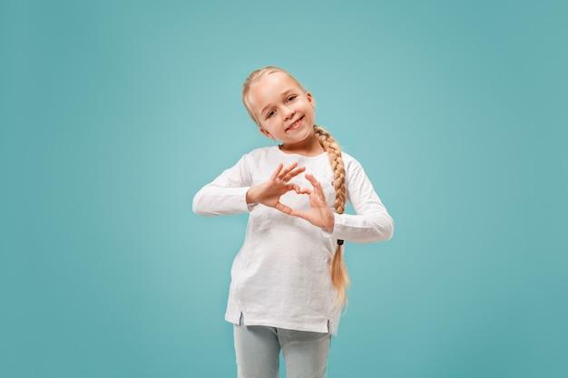 Het mooie glimlachende tienermeisje maakt de vorm van een hart met haar handen op het blauw Gratis Foto