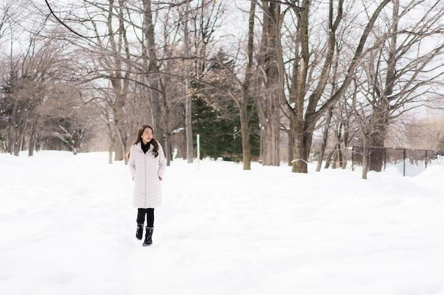 Het mooie jonge aziatische vrouw glimlachen gelukkig voor reis in sneeuw wintertijd Gratis Foto