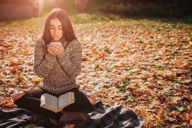 Het mooie jonge brunette zit op gevallen herfstbladeren in een park, drinkt het vrouwelijke model thee of koffie en leest een boek Premium Foto