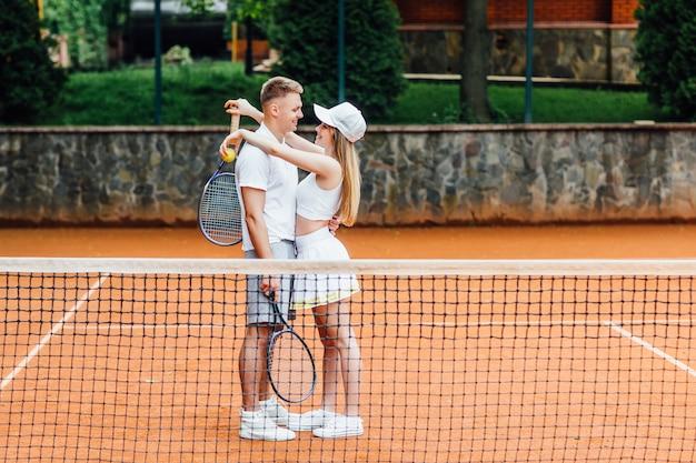 Het mooie jonge, leuke paar speelt in openlucht tennis bij zonnig weer, glimlacht het meisje. Premium Foto