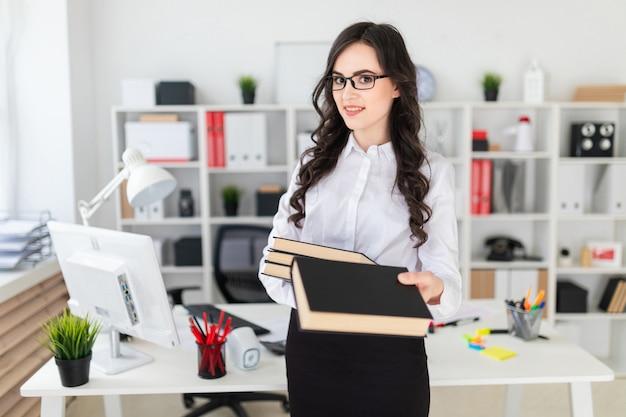 Het mooie jonge meisje bevindt zich in het bureau, houdt een stapel boeken in haar handen en één zich vooruit uitrekt Premium Foto