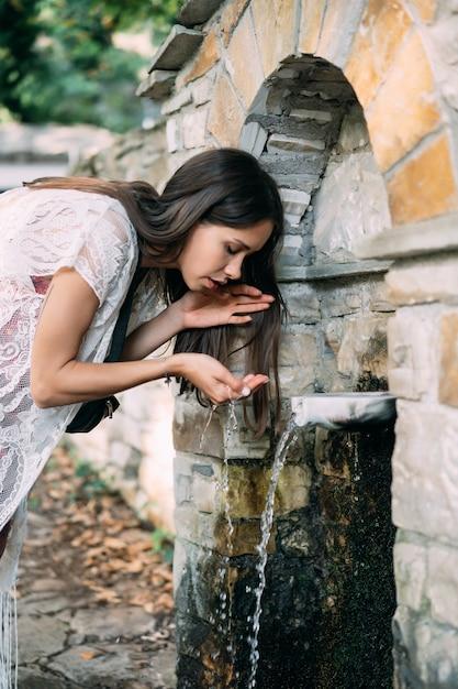 Het mooie, jonge meisje drinkt bronwater openlucht Gratis Foto