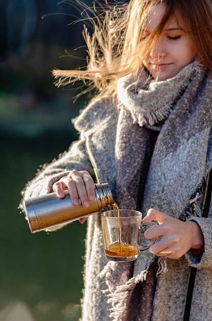 Het mooie jonge meisje giet aftreksel uit een thermosfles in een glazen mok Premium Foto