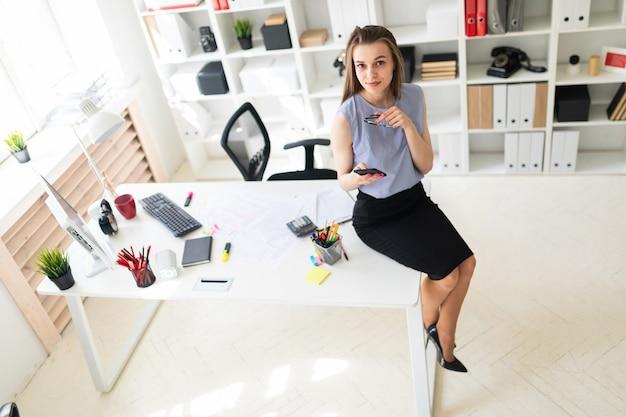 Het mooie jonge meisje in het bureau zit bij het bureau en houdt glazen en een telefoon. Premium Foto