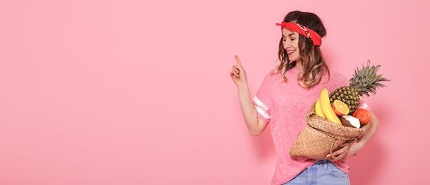 Het mooie jonge meisje in roze t-shirt, houdt een volledige strozak fruit op roze achtergrond Gratis Foto