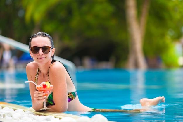 Het mooie jonge meisje ontspannen in het zwembad Premium Foto