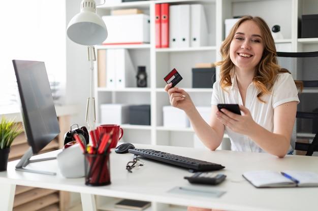 Het mooie jonge meisje zit in het bureau, houdt een betaalpas en een telefoon in haar hand. Premium Foto