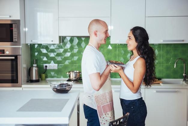 Het mooie jonge paar bracht het miling bij de camera in kaart terwijl thuis het koken in de keuken. Premium Foto