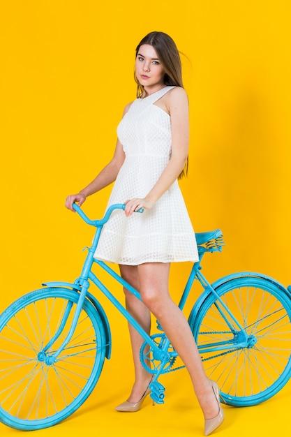 Het mooie jonge vrouw stellen gezet op een blauwe fiets Premium Foto