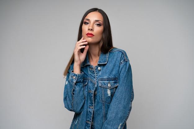 Het mooie kaukasische het denimjasje van het meisje stellen Premium Foto