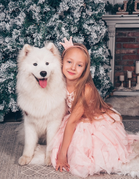 Het mooie kleine blonde meisje glimlacht met een witte grappige samojeed-hond bij de nieuwjaarsboom. Premium Foto