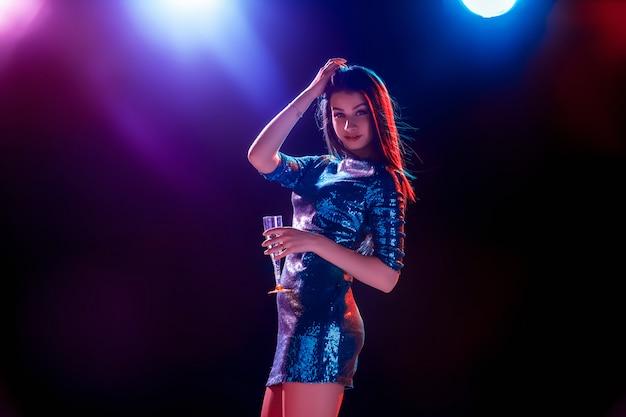 Het mooie meisje dat op het feest danst en champagne drinkt Gratis Foto