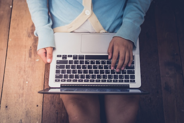Het mooie meisje gebruikte laptop en koffiekop in de handen die van het meisje op een houten vloer zitten Premium Foto