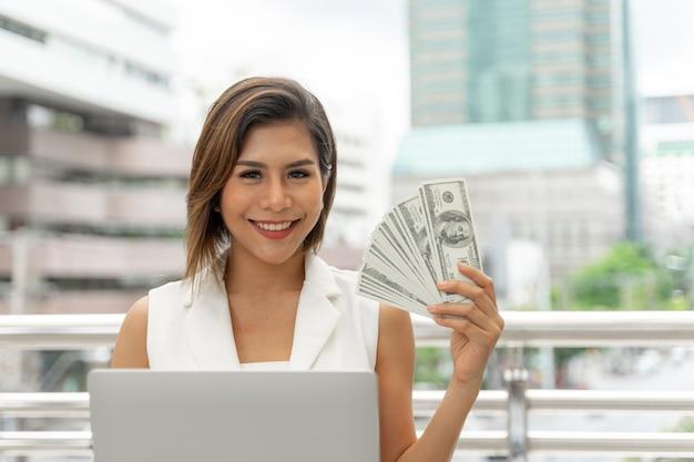 Het mooie meisje glimlachen in bedrijfsvrouwenkleren gebruikend laptop computer en toont ter beschikking de rekeningen van de geldamerikaanse dollar Gratis Foto