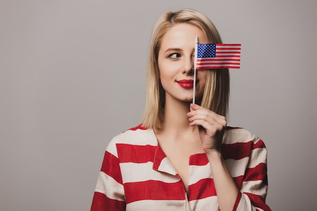Het mooie meisje houdt de vlag van de verenigde staten van amerika Premium Foto