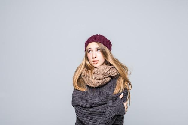 Het mooie meisje in grijze sweater probeert koud op grijs op te warmen Gratis Foto