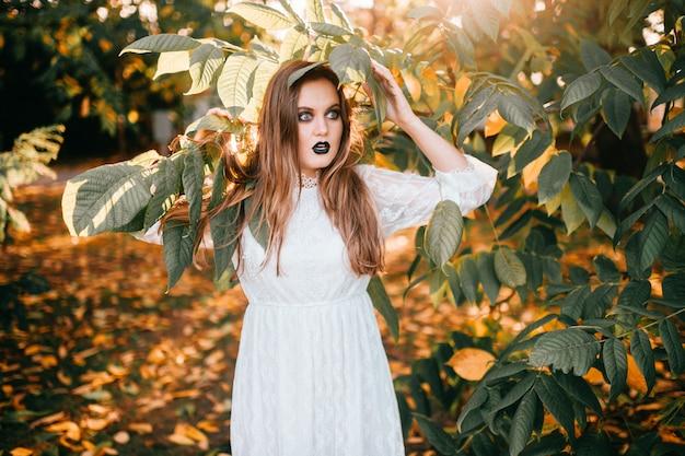 Het mooie meisje met gotisch maakt omhooggaande en het grappige gezichtsuitdrukking stellen in de zomerpark. Premium Foto