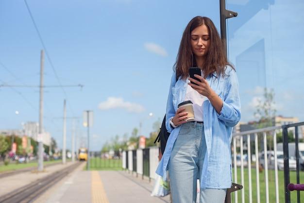 Het mooie meisje met kop van koffie wacht op bus of tram op openbaar vervoerpost in de ochtend. jonge vrouw met slimme telefoon monitoring transport via de app. Premium Foto