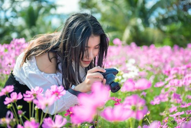 Het mooie meisje neemt een foto aan kosmosbloem in tuin. Premium Foto