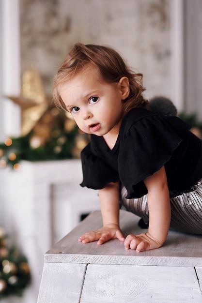 Het mooie meisje spelen dichtbij kerstboom thuis Premium Foto