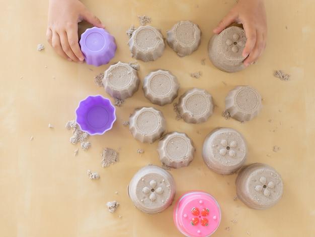 Het mooie meisje spelen met kinetisch zand thuis Premium Foto