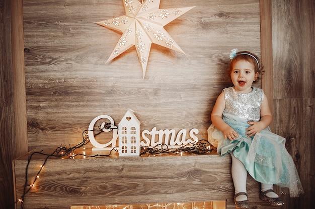 Het mooie meisje stellen in comfortabele die ruimte voor kerstmis wordt verfraaid Premium Foto