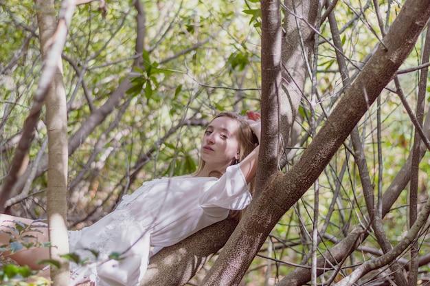 Het mooie meisje stellen liggend op een boom Gratis Foto