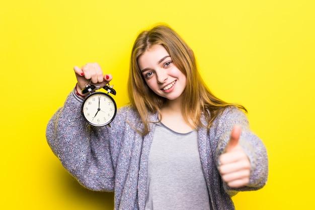 Het mooie meisje van de studententiener met wekker met omhoog geïsoleerde duimen Gratis Foto