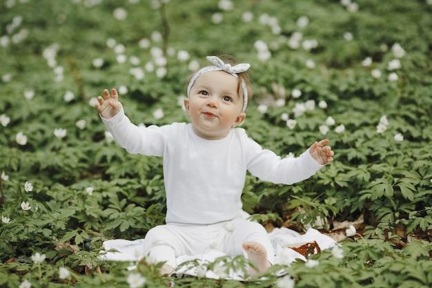 Het mooie meisje verheugt zich in het bos onder de bloemen Gratis Foto