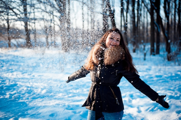 Het mooie meisje werpt sneeuw in een de winterpark Premium Foto