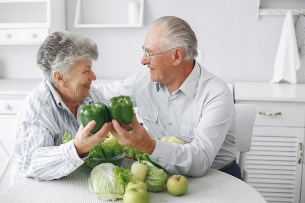 Het mooie oude paar bereidt voedsel in een keuken voor Gratis Foto